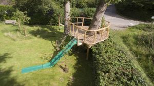 birdseye view wooden treehouse platform with slide and rope rigging