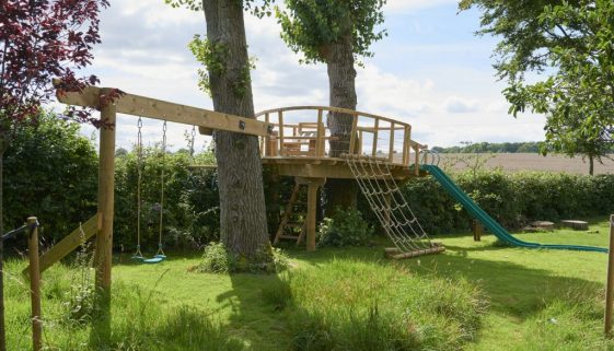 ground view of treehouse platform with swings slide and rope rigging