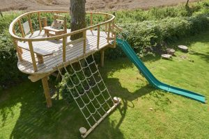 wooden treehouse platform with slide and rope rigging
