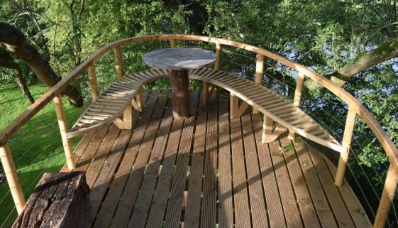 wooden treehouse platform with table and benches