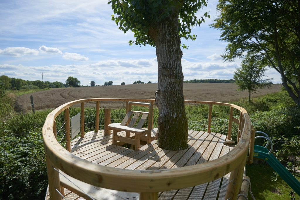 rounded treehouse platform overlooking field